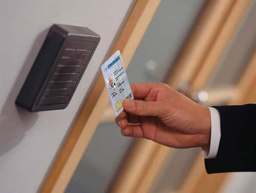 Man waving a card key in front of a wall-mounted card reader