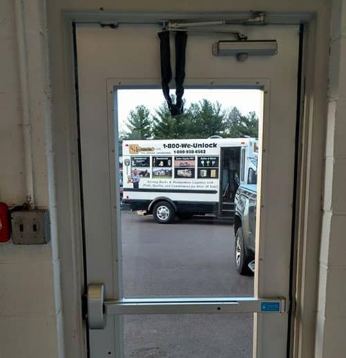 image of a commercial door with a new panic bar and door closer that we installed